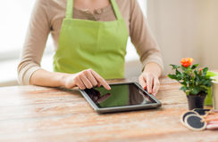 Close up of woman or gardener with tablet pc. People, gardening, flowers and profession concept - close up of woman or gardener with tablet pc computer at home Royalty Free Stock Images