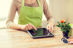 Close up of woman or gardener with tablet pc. People, gardening, flowers and profession concept - close up of woman or gardener with tablet pc computer at home Stock Image