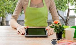 Close up of woman or gardener with tablet pc. People, gardening, flowers and profession concept - close up of woman or gardener with tablet pc computer sitting Royalty Free Stock Photos
