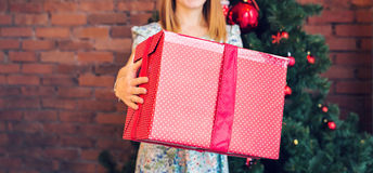 Close-up of woman with a gift box over christmas tree background Royalty Free Stock Photography
