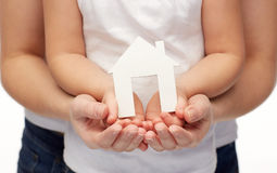 Close up of woman and girl hands with paper house Royalty Free Stock Images