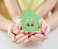 Close up of woman and girl hands with paper house Royalty Free Stock Photo