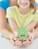 Close up of woman and girl hands with paper house Stock Images