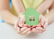 Close up of woman and girl hands with paper house. People, charity, family and home concept - close up of women and girl holding green paper house cutout in Royalty Free Stock Image