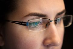 Close up of woman in glasses looking at screen royalty free stock photography