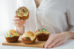 Close up of woman with glazed cupcakes or muffins Stock Photos