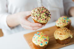 Close up of woman with glazed cupcakes or muffins Royalty Free Stock Image