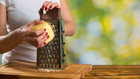 Close-up of a woman grating parmesan cheese. Stock Photography