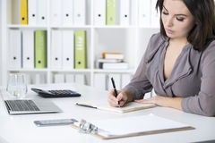 Close up of a woman in gray writing Royalty Free Stock Photos