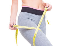 Close-up of woman at gym measuring her thigh Stock Photography