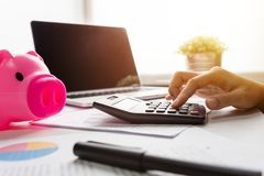 Close up of woman hand calculating her monthly expenses. Pink Piggy Bank, Laptop, Calculator, business chart and graph document on desk. Debt Stock Images