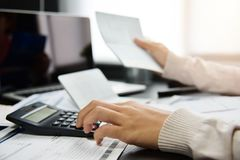Woman calculating her Debt. Close up of woman hand calculating her monthly expenses.  Debt Stock Photos