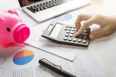 Close up of woman hand calculating her monthly expenses. Pink Piggy Bank, Laptop, Calculator, business chart and graph document on desk. Debt Stock Photo