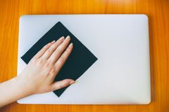 Laptop clean. Close-up Of Woman Hand Cleaning Laptop With Laptop At Home royalty free stock image