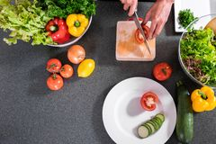 Close up of woman hand cutting tomato on chopping wood board wit. H sharp knife and cooking vegetables salad in kitchen, top view Stock Images