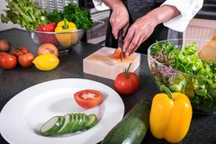 Close up of woman hand cutting tomato on chopping wood board wit. H sharp knife and cooking vegetables salad in kitchen Stock Photos