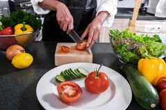 Close up of woman hand cutting tomato on chopping wood board wit. H sharp knife and cooking vegetables salad in kitchen Stock Photo