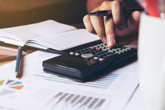 Close up woman hand doing finance and calculate about cost on de Royalty Free Stock Photos