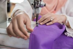 Woman fashion designer working. Close up of woman hand fashion designer work using sewing machine in the office Stock Image
