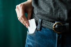Close Up woman hand grabbing a white card in jeans pocket royalty free stock photography