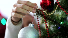 Close-up woman hand is hanging Christmas toy on the branch of Christmas tree stock video