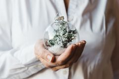 Close-up of woman hands holding Christmas bauble. Close-up of woman hand holding Christmas bauble. Focus on foreground Stock Photography