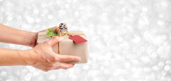 Close up woman hand holding Christmas present box with silver sp. Arkle bokeh background,Banner mock up for adding your text,Gift giving on holiday seasonal Royalty Free Stock Images