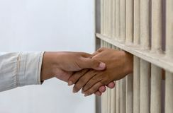 Hold hands with a female friend in a prison. Close-up of a woman hand holding a hand of friends who illegally and was arrested in prison, poorly nicked royalty free stock images