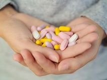 Close-up woman hand holding a lot of different pills. Health care and medical concept Stock Photos