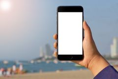 Close-up Woman hand holding mobile phone on beatiful fresh sea sand and blue sky background. Mock-up smartphone blank screen royalty free stock photos