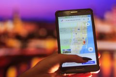Map of Florida on the phone in the background of a night city. Close Up Of Woman Hand Holding Mobile Phone. Close Up Of Woman Hand Holding Mobile Phone. map of royalty free stock photo