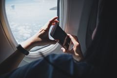 Close up woman hand holding mobile phone and take a photo outside airplane window. royalty free stock images