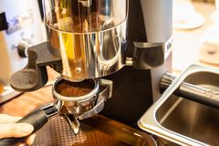 Close up woman hand holding portafilter, girl barista is grinding the roasted coffee beans into powder using coffee grinder at. Cafe shop royalty free stock photos