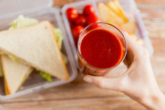 Close up of woman hand holding tomato juice glass Stock Images