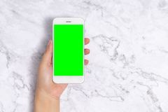 Close up woman hand holding white mobile phone with blank green screen on white marble background, front view with copy space. stock photography