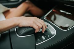 Female arm situating on vehicle gear shift. Close up woman hand locating on get lever of contemporary cozy automobile cabin royalty free stock photography