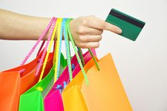 Close up woman hand with many shopping bags and credit card isolated on white background Stock Photo