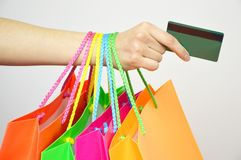 Close up woman hand with many shopping bags and credit card isolated on white background Royalty Free Stock Image