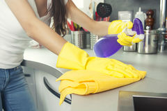 Close up of woman hand in protective glove with rag cleaning coo stock photography