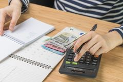 Close up of woman hand pushing button on calculator with list of budget, expense and cost on small notepad, pile of money and royalty free stock photos