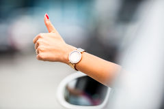 Close-up of a woman hand showing a thumbs-up sign out with car windows.  Stock Images