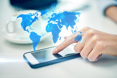 Close up of woman hand with smartphone and map. Business, technology, global communication and people concept - close up of woman hand with smartphone and coffee Stock Photography