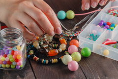 Close up of woman hand threading beads Royalty Free Stock Photo