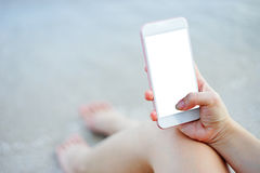 Close up of woman hand using smart phone at beach.technology concept.blurred beach sea background.clipping path included. Royalty Free Stock Photos