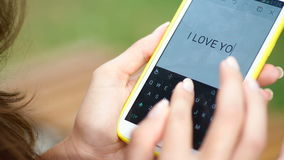 Close up woman hand using smartphone and touching on a blank screen park outdoor.  stock footage