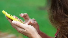 Close up woman hand using smartphone and touching on a blank screen park outdoor.  stock video footage
