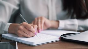 Close up woman hand write notes with pen in notebook, slow motion. Businesswoman writes to do list in diary stock footage