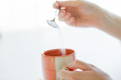 Close up of woman hands adding sugar to tea cup Stock Image