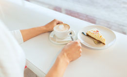 Close up of woman hands with cake and coffee Stock Image
