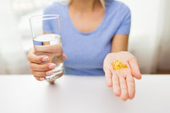 Close up of woman hands with capsules and water Stock Photos